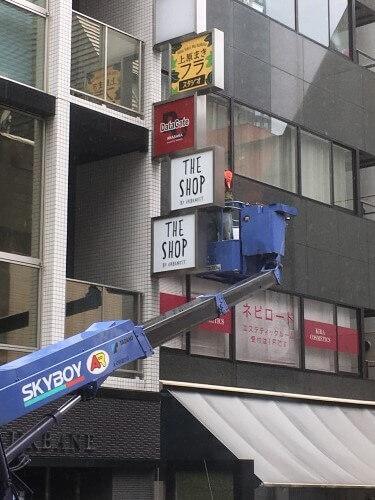 ビルの突き出し看板の裏側から工事